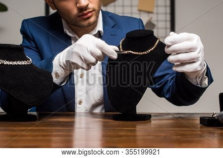 Cropped View Of Jewelry Appraiser In Gloves Holding Tweezers Near Necklace On Necklace Stand On Tabl