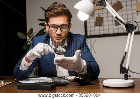 Jewelry Appraiser Examining Bracelet With Magnifying Glass Near Jewelry On Table