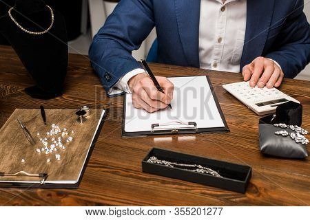 Cropped View Of Jewelry Appraiser Using Calculator And Writing On Clipboard Near Jewelry On Wooden T