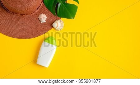 Sunscreen Lotion In White Plastic Bottle, Beach Hat And Tropical Leaf On Yellow Background. Sun Prot