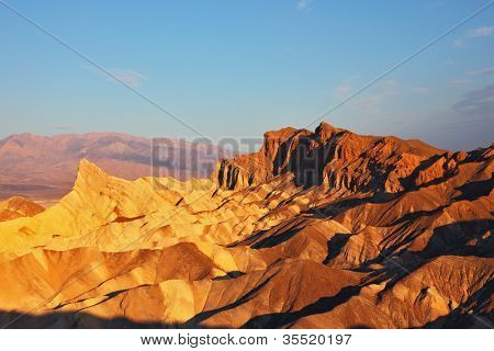 The well-known site of Death valley in California - the Zabriski-point. Picturesque hills of pink, yellow and chocolate shades on a sunset