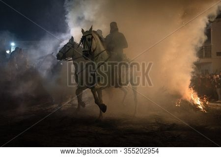 Rider Riding His Horse, Jumping Fire Fire To Purify The Animal, In A Religious Event Held In The Tow