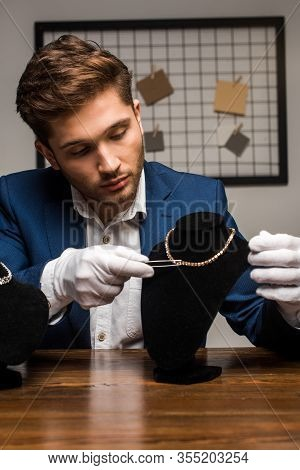Handsome Jewelry Appraiser Holding Tweezers Near Necklace On Pedestal On Table In Workshop