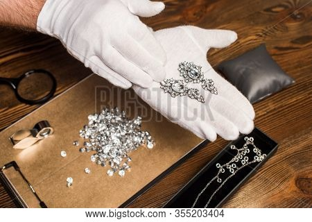 Cropped View Of Jewelry Appraiser Holding Earrings Near Gemstones And Magnifying Glasses On Board On