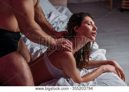Cropped View Of Shirtless Man Making Shoulders Erotic Massage To Sexy Girlfriend Lying On Bed With C