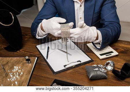 Cropped View Of Jewelry Appraiser Holding Necklace Near Calculator, Clipboard And Jewelry On Table