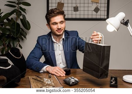 Handsome Jewelry Appraiser Holding Paper Bag Near Earrings And Necklaces On Table
