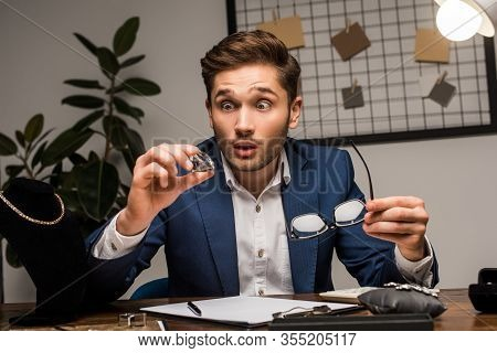 Existed Jewelry Appraiser Holding Gemstone And Eyeglasses Near Jewelry On Table In Workshop