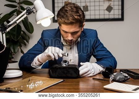 Jewelry Appraiser With Magnifying Glass Examining Gemstone Near Jewelry On Table In Workshop