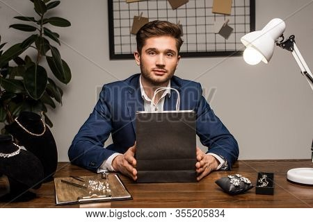 Handsome Jewelry Appraiser Looking At Camera While Holding Paper Bag Near Jewelry On Table In Worksh