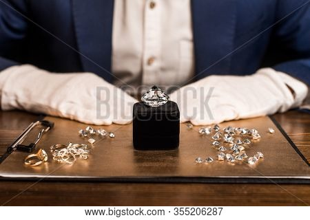 Cropped View Of Gemstone Near Jewelry On Board And Jewelry Appraiser At Table Isolated On Black