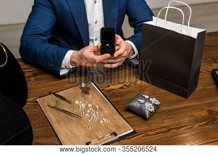 Cropped View Of Jewelry Appraiser Holding Box With Ring Near Jewelry And Paper Bag On Table In Works