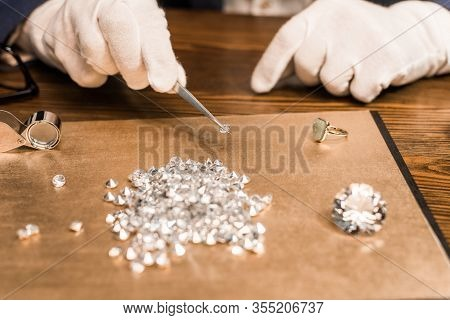 Cropped View Of Jewelry Appraiser Holding Gemstone In Tweezers Near Board On Table