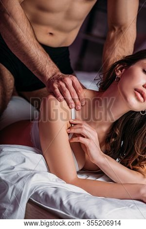 Cropped View Of Sexy Man Making Shoulders Erotic Massage To Seductive Girlfriend Lying In Bed