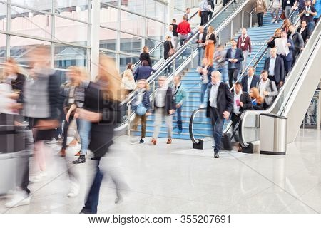 Large anonymous crowd of business people on stairs at airport or shopping mall