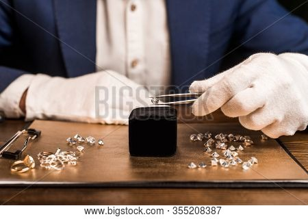 Cropped View Of Jewelry Appraiser Holding Gemstone In Tweezers Near Jewelry On Board On Table Isolat