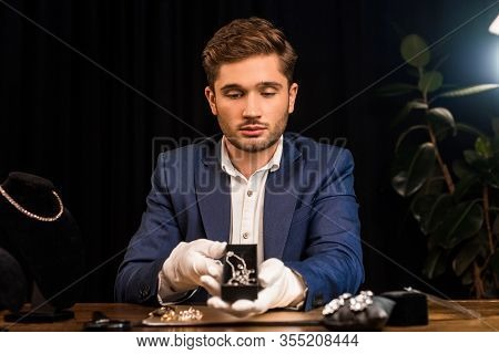 Handsome Jewelry Appraiser Holding Box With Necklace Near Jewelry On Table In Workshop