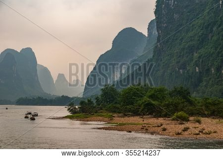 Guilin, China - May 10, 2010: Along Li River. Landscape With 5 Small Boats Approaching With Tall Kar