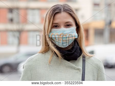 Girl With Mask To Protect Her From Corona Virus. Corona Written On Mask. Woman With Mask Standing In