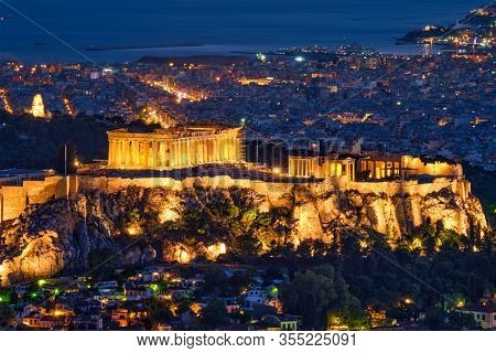 Parthenon Temple on hill is the antique tourist landmark at the Acropolis of Athens and ancient European civilization architecture on Aegean sea coast. Dusk view from Mount Lycabettus, Athens, Greece