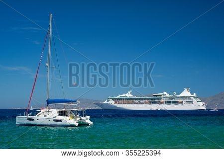 Catamaran yacht and cruise liner is Aegean sea on beautiful summer day. Chora, Mykonos island, Greece