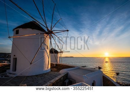 Scenic view of famous Mykonos town windmills. Traditional greek windmills on Mykonos island on sunset with dramatic sky, Cyclades, Greece. Walking with steadycam.