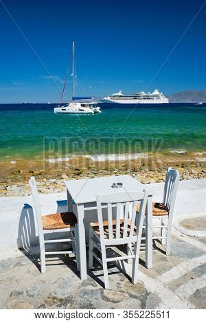 Tourist greek scene - restaurant cafe table on quay promenade with catamaran yacht and cruise liner and Aegean sea in background on beautiful summer day. Chora, Mykonos island, Greece