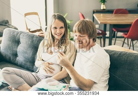Happy Pregnant Couple Checking Baby Clothes In Living Room. Expectant Parents Sitting On Couch, Hold