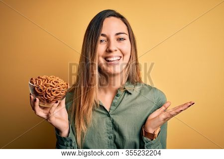 Young beautiful blonde woman with blue eyes holding bowl with german baked pretzels very happy and excited, winner expression celebrating victory screaming with big smile and raised hands