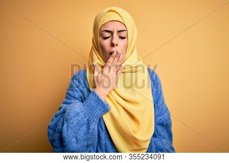 Young beautiful brunette muslim woman wearing arab hijab over isolated yellow background bored yawning tired covering mouth with hand. Restless and sleepiness.