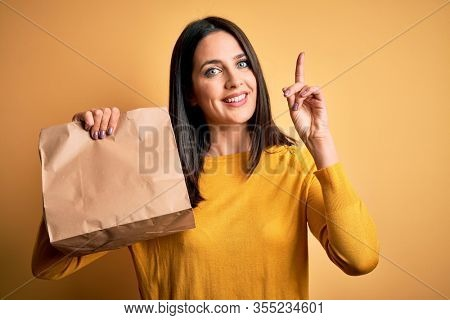 Young brunette woman with blue eyes holding delivery paper bag with food surprised with an idea or question pointing finger with happy face, number one