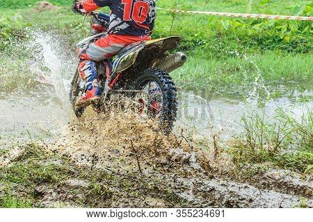 Motocross,enduro Rides Through The Mud With Big Splash,driver Splashing Mud On Wet And Muddy Terrain