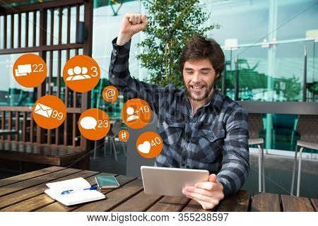 Happy Man Using Tablet And Celebrating Achievement In Cafe With Social Media Icons. Attractive Guy R