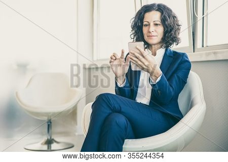 Satisfied Customer With Cell Browsing Web Pages. Business Woman Sitting In Armchair, Using Mobile Ph