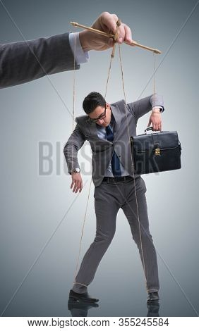 Businessman puppet being manipulated by boss