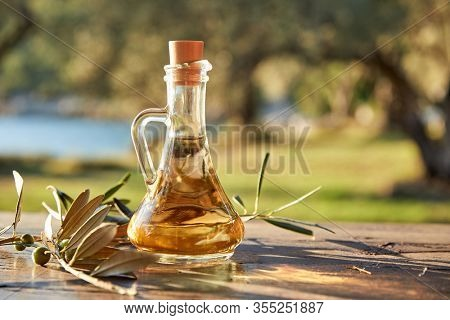olive oil in the bottle and branch of green olives
