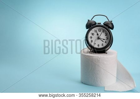 Alarm Clock And Toilet Paper On Blue Background