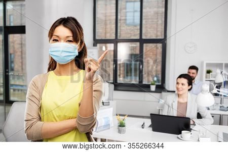 health, safety and pandemic concept - asian young woman wearing protective medical mask for protection from virus disease over office background