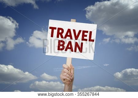 Travel Ban Message On Board In Hand With Sky Background