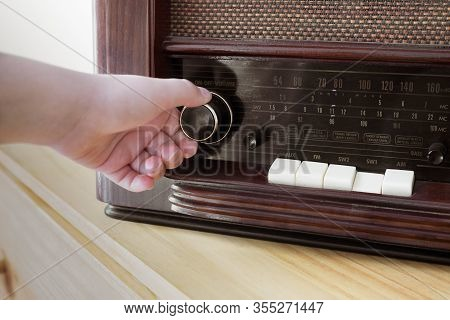 A Woman Hand Adjusting The Button Vintage Radio Volume For Listen Music Or News