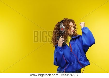 Enjoy Listening To Music. Beautiful Young Curly-haired Woman With Headphones Listening Music, Singin
