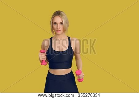 Pretty Blond Woman In Black Training Top With Small Pink Dumbbells In Her Hands, Looking At Camera.