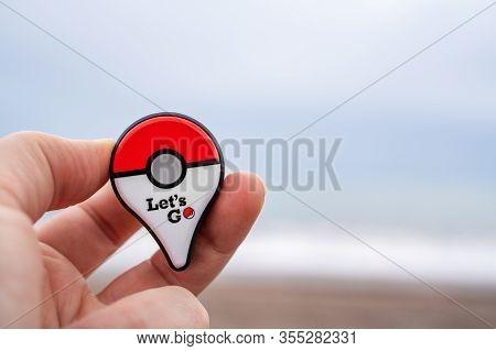 Budva, Montenegro March 07, 2020: Player Holding New Pokemon Go Plus Against The Sea. Pokemon Go Is