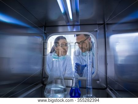 Two Biologists Looking Through Glass Door Into Incubator With Samples And Chemicals In Laboratory. S