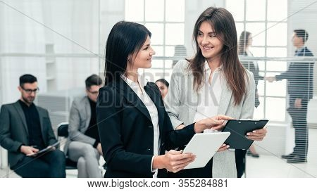 Two Business Women Discussing Business Documents In The Office