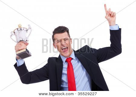 victory roar of a young businss man with a big trophy cup on white background