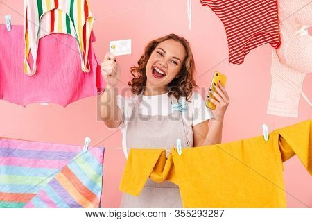 Image of smiling happy optimistic woman housewife isolated over pink wall background dry clothes on rope using mobile phone holding credit card.