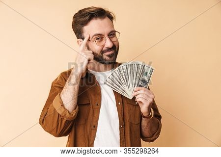 Image of a smiling positive young unshaved man isolated over beige wall background holding money.