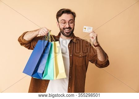 Image of a happy smiling young unshaved man isolated over beige wall background holding credit card and shopping bags.