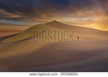 Single Photographer Standing In Curved Ibex Dunes In Death Valley At Sunset